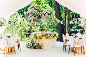 luxury wedding decor. Wedding in white and gold colors. elegant wedding decorated with white flowers. tropical flowers at the wedding. Wedding in a white tent. white table of the bride and groom.