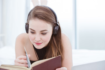 beautiful girl teen relax at home to reading a book and listening music