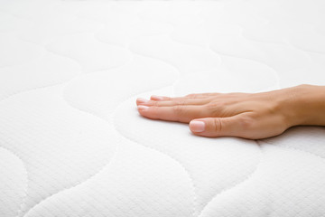 Woman's hand touching cloth white mattress. Checking softness. Choice of the best type and quality. Side view. Closeup.