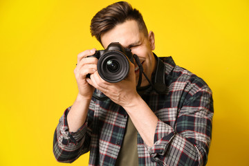 Young male photographer on color background