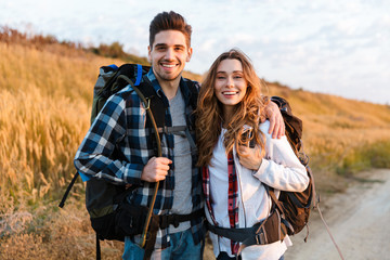 Cheerful young couple carrying backpacks hiking together Wall mural