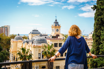 woman with blue shirt enjoys the view over the town of Malaga, Spain