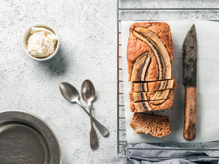 Butter-free, sugar-free banana bread with oat flour, soft curd cheese and honey. Top view of sliced banana bread on gray cement background. Ideas and recipes for healthy diet breakfast