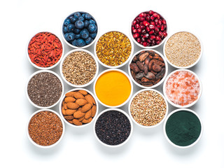 Various superfoods in smal bowl isolated on white background. Superfood as chia, spirulina, raw cocoa bean, goji, hemp, quinoa, bee pollen, black sesame, turmeric. Top view or flat-lay.