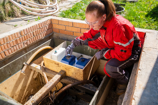 woman worker in uniform serves an autonomous sewer. top view. Processing station biological water purification.