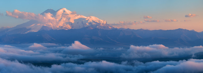 Wall Mural - Beautiful sunset in the Caucasus Mountains, view towards Elbrus from the Bermamyt plateau. Snow-capped peaks above the clouds. Tourism in Russia.