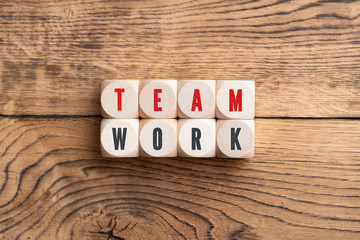 """cubes showing the message """"teamwork"""" on wooden background"""