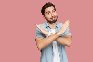 Portrait of serious handsome bearded young man in blue casual style shirt standing with X sign hands and looking at camera. indoor studio shot, isolated on pink background. Wall mural