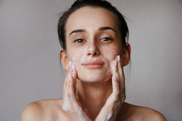 Fototapeta girl washing her face with a cleansing gel in the bathroom obraz