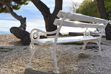 Empty white wooden bench in the rays of the setting sun with highlights. On the shores of the azure...