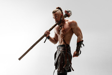 Serious long hair and muscular male model in leather viking's costume with the big mace cosplaying isolated on white studio background. Half-length portrait. Fantasy warrior, antique battle concept.