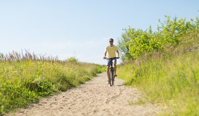 people, sport and lifestyle concept - happy smiling young man in sunglasses riding bicycle outdoors