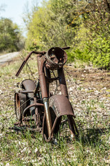 Rusted frame of a motorcycle  an abandoned village in Belarus, Chernobyl exclusion zone