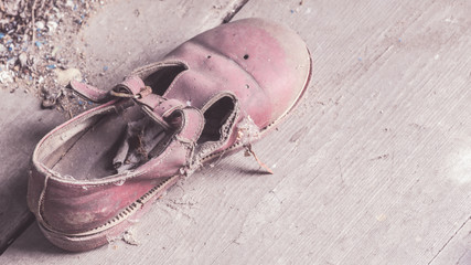 Abandoned little child shoe covered with dust in a  collapsed  house in Belarus, Chernobyl exclusion zone
