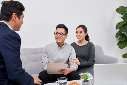 Sales Consultant showing new investment plans to young asian couple