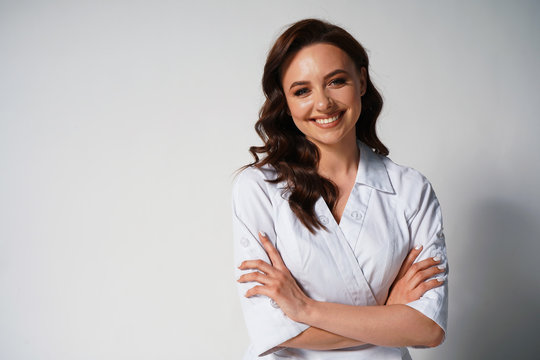 Portrait of beautiful young female doctor in white medical jacket isolated on white background. Brunette woman cosmetologist smiling at the camera. Cross hands. Space for text