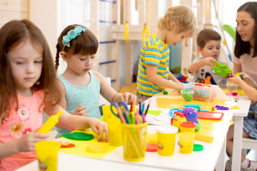 Group of preschool kids engaged in handcrafts. Children and teacher in classroom