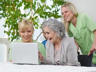 Seniorin mit Pflegern am Laptop
