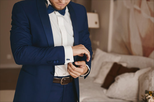 Handsome bearded brutal man in a stylish blue suit and in bowtie puts on stylish cufflinks and posing at interior