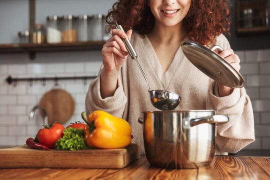 Photo of attractive caucasian woman holding cooking ladle spoon while eating soup at home