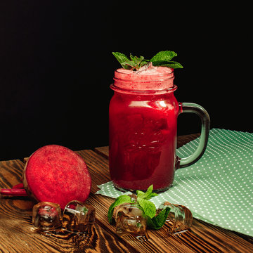 beet lemonade in a glass with mint leaves on a wooden background