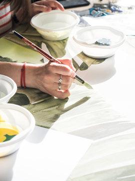 Crop woman painting leaves
