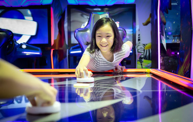 Asian little girl playing arcade game on the computer machines at the shopping mall outlets,holiday activities of cute child play games,slot machines in the mall center,vacation concept.