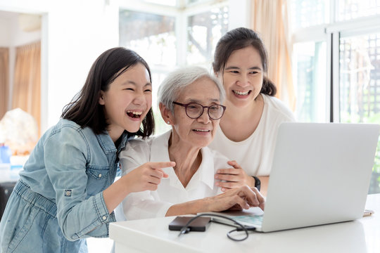 Mother and daughter watching something interesting with grandmother,happy smiling asian senior woman while her daughter and granddaughter using laptop computer in home,concept family,technology