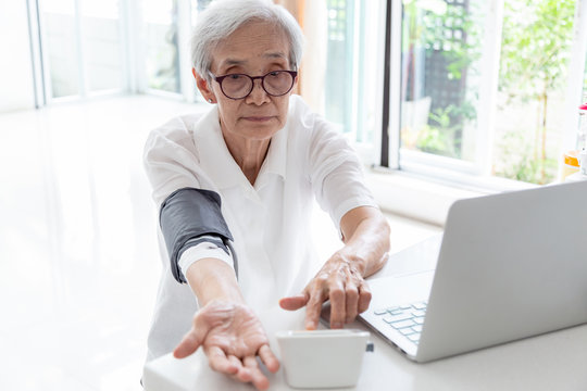 Senior woman checking blood pressure with device and laptop