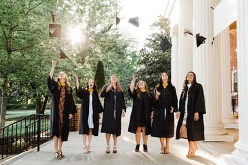 Female Graduates tossing caps into the air