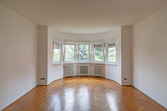 Empty Room with large bay window and hardwood floor after renovation