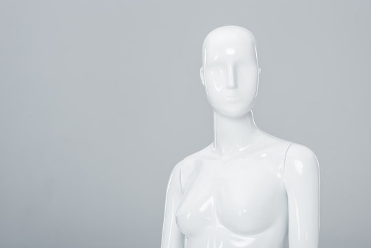 white plastic mannequin figure isolated on grey with copy space