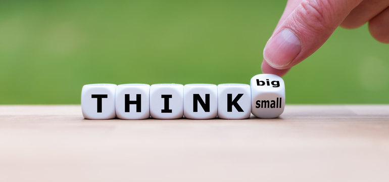 "Hand turns a dice and changes the expression ""think small"" to ""think big""."