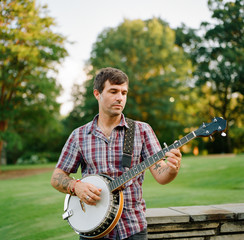 Handsome man playing banjo in a park