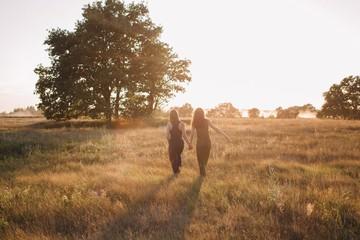 Two unrecognizable girlfriends walking by summer field in sunset light
