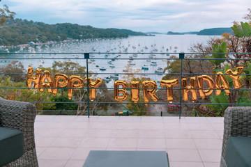 happy birthday balloons on veranda railing