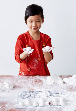 Beautiful cute Asian little girl, happy to make Chinese dessert rice dumpling at home