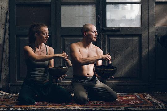 Man and woman meditating with spiritual items