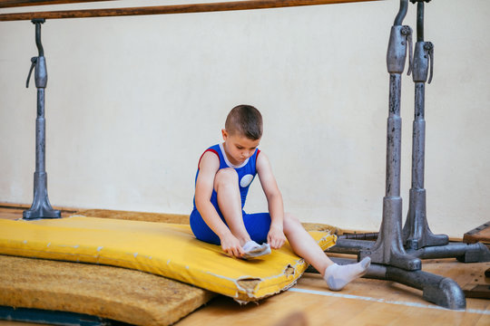 Young boy sitting on the floor and putting socks