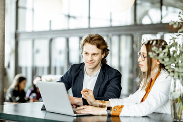 Young man and woman having a business conversation while sitting with laptop at the bar or modern...