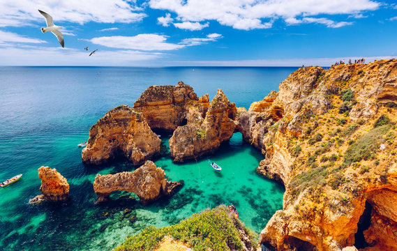 Panoramic view, Ponta da Piedade with seagulls flying over rocks near Lagos in Algarve, Portugal. Cliff rocks, seagulls and tourist boat on sea at Ponta da Piedade, Algarve region, Portugal.