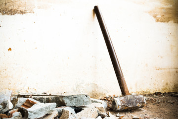 A hammer used to demolish the concrete tile floor and wall of the house before renovation. It heavy and very hard because it made from metal.