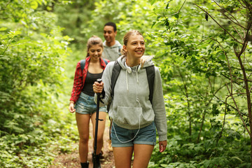Group of friends hiking in nature.Girl with blond hair  lead the group.