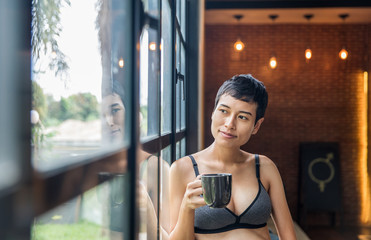 Short haired woman in a bra looking out the window