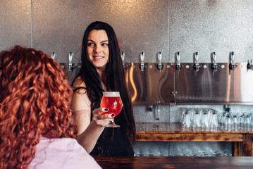 Female bartender serving craft beer at a micro brewery bar
