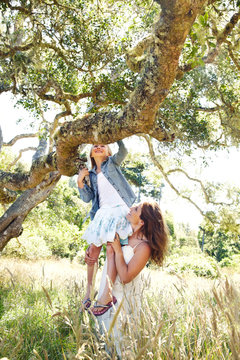 Little girl climbing a tree with her mom helping her
