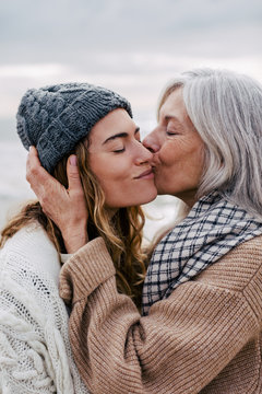 Senior woman kissing her daughter on the beach.