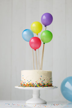 Birthday cake decorated with colorful balloons