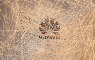 A scratched surface Huawei logo is seen on a smarthphone in this illustration picture