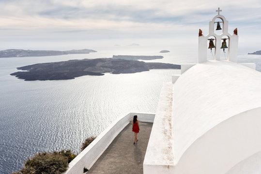 Girl walking near orthodox church at Santorini, Greece